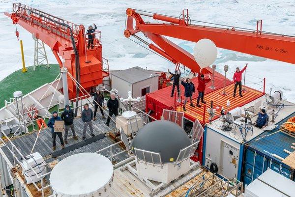 Gruppenfoto des ATMOS-Teams auf dem Vordeck der Polarstern. Rechts unten im Bilder der weiße OCEANET-Container des TROPOS mit unserem Kollegen Martin. Foto: Christian Rohleder, DWD