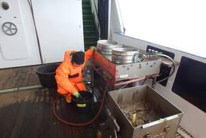 Der an Deck kommende Schlamm wird vorsichtig aufgerührt, sodass das sehr feine Sediment durch eine Siebreihe durchgespült werden kann. Foto: AWI