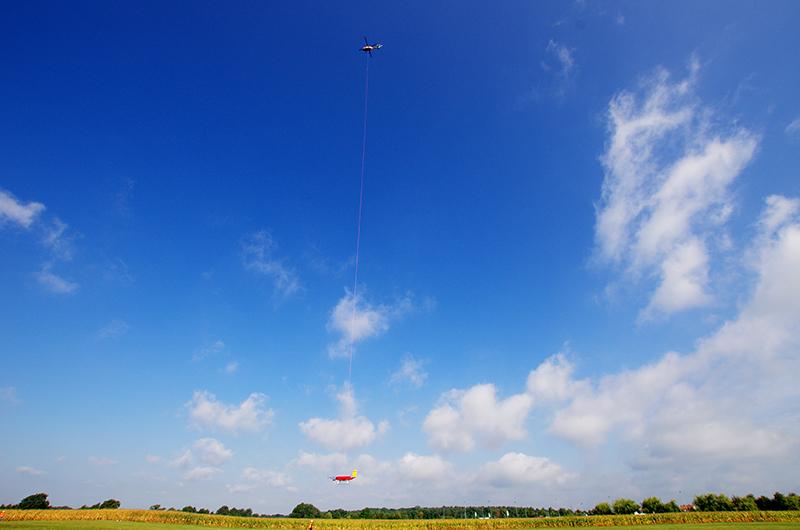 Die mit verschiedensten Sensoren ausgestattete Hubschrauberplattform ACTOS und der Schleppkörper SMART-Helios werden hängen an einem langen Seil und werden per Hubschrauber zu den Wolken gebracht. Foto: Holger Siebert, TROPOS