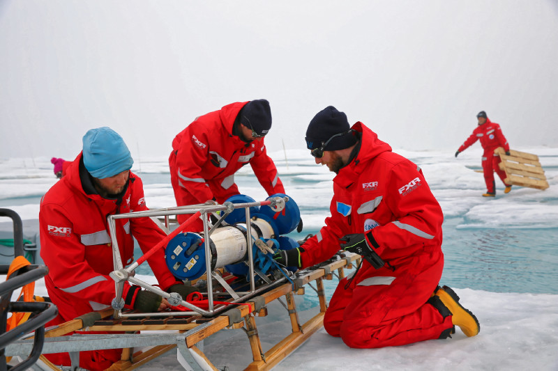All teams work together to recover instruments from the central observatory on the ice floe. The so-called ADCP (Acoustic Doppler Current Profiler) for oceanographic measurements has been deployed in the ocean under the ice and is now fixed on a sledge to transport it back home to Plarstern. Photo: Lisa Grosfeld, AWI