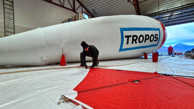 The tethered balloon BELUGA is being prepared for ascent in a hangar in Ny-Ålesund. Michael Lonardi from the University of Leipzig assembles the tail unit that stabilises the balloon in the air.  Photo: André Ehrlich, Leipzig University