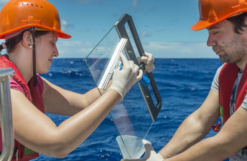 Zur Probenahme wird eine Glasplatte ins Wasser getaucht und anschließend wieder vorsichtig aus dem Wasser gezogen. Dabei bleibt der 200 Mikrometer dünne Oberflächenfilm am Glas haften und wird anschließend abgekratzt. Foto: Hartwig Deneke/TROPOS